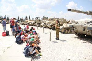 ילדים מקשיבים להדרכה של חיילת על טנקים