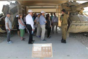 גברים ונשים מאזינים להרצאה של חייל הנשען על טנק