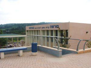 ספסל ממתכת ולידו פח כחול גם כן ממתכת מולה בניין עם כיתוב בכחול מורשת קרית חינוך לערכים וטבע