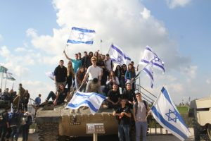 נערים על טנק עם דגלי ישראל
