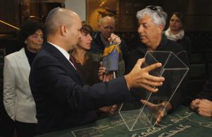 """יו""""ר העמותה האלוף (במיל') אודי שני מסביר בבית הכנסת """"צרור החיים"""" על דרכו של ספר התורה הקטנטן מיהודי אירופה ליד לשריון"""