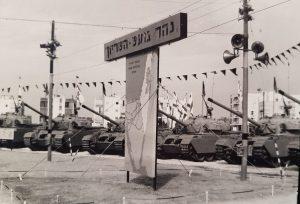 """שלט בחניון - """"נהר גועש - השריון"""". וברקע טנקי 'שוט' (טנק צנטוריון עם מנוע בנזין מדגם מטאור) של חטיבה 7."""