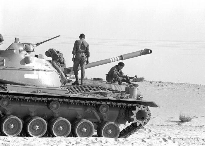 חיילים יושבים על טנק ישן