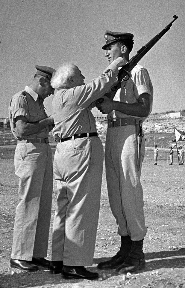 """ראש הממשלה דוד בן גוריון מעניק סיכת מ""""מ למשה לוי, לימים הרמטכ""""ל. משמאל ישראל טל """"טליק"""""""