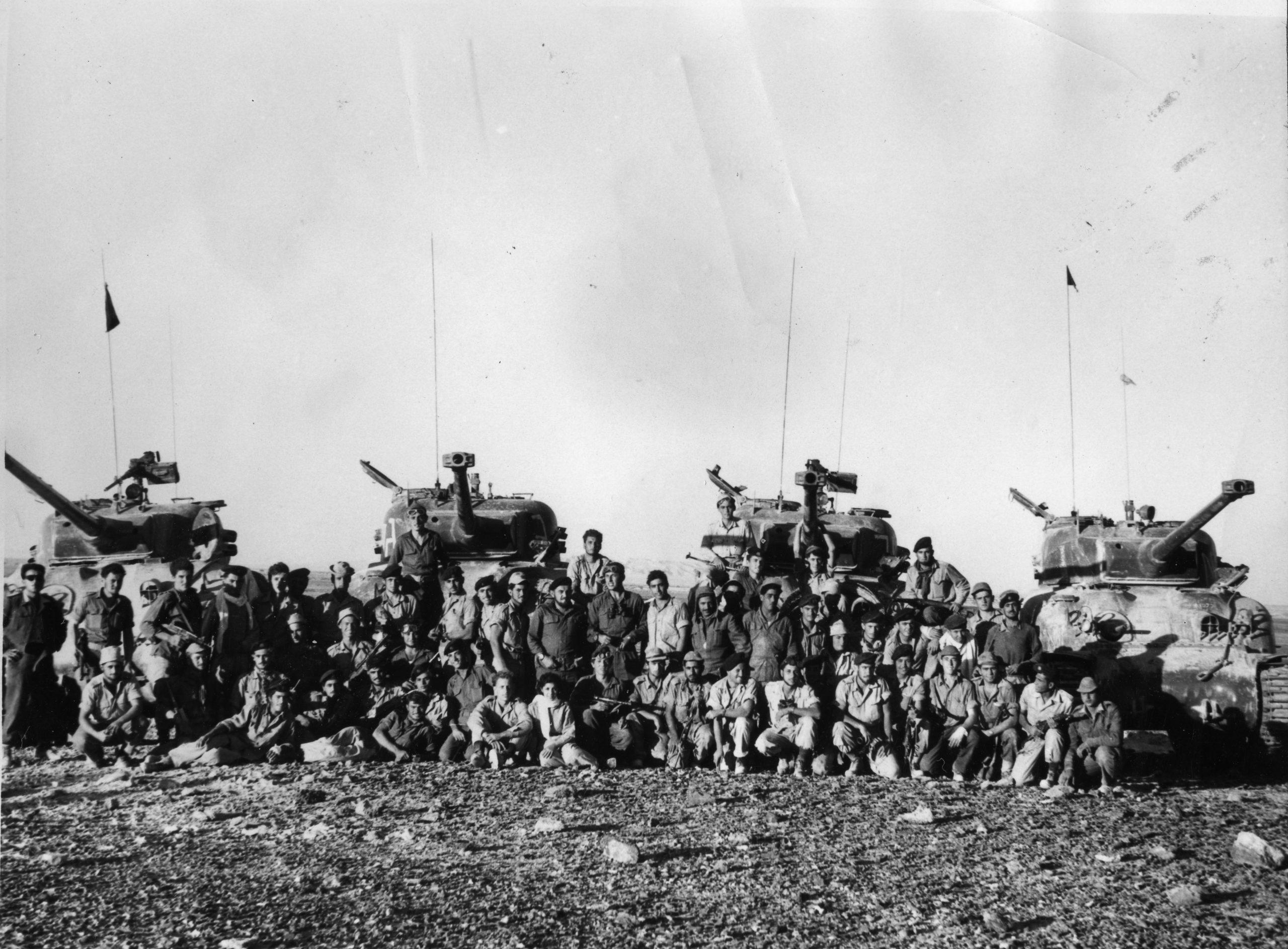 """לוחמי פלוגה א' מגדוד 82 לאחר מבצע קדש, מצוידים בטנקי שרמן M50 שאך עברו הסבה לתותח צרפתי 75 מ""""מ. במרכז עם המשקפת , המ""""פ משה בריל בר-כוכבא. (צילום: אוסף בן-ארי)"""