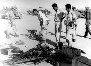 """המ""""פ משה בריל בוחן שלל מצרי לאחר הקרב, בין היתר מכונת כתיבה ששימשה את המפקדה המצרית. (צילום: אוסף בן-ארי)"""